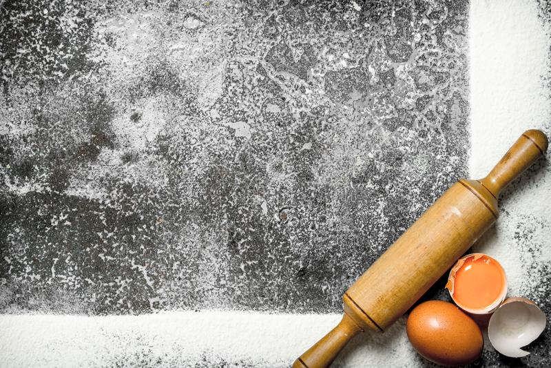 Stekhet bakgrund En ram av mjöl med en kavel och nya ägg royaltyfria bilder