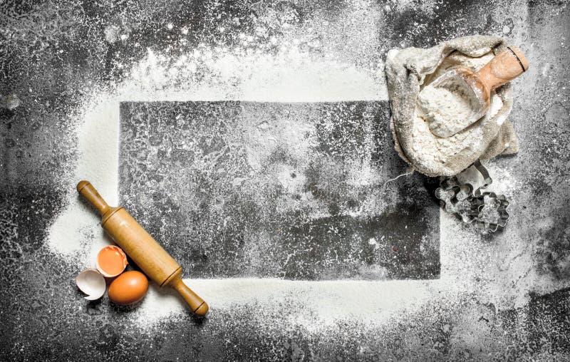 Stekhet bakgrund En ram av mjöl med en kavel och nya ägg royaltyfri fotografi