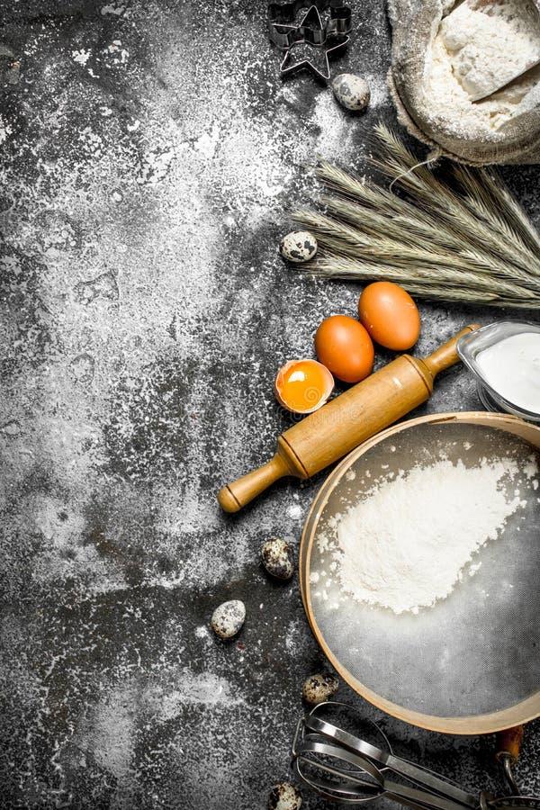 Stekhet bakgrund Ingredienser och hjälpmedel för degförberedelse royaltyfri bild