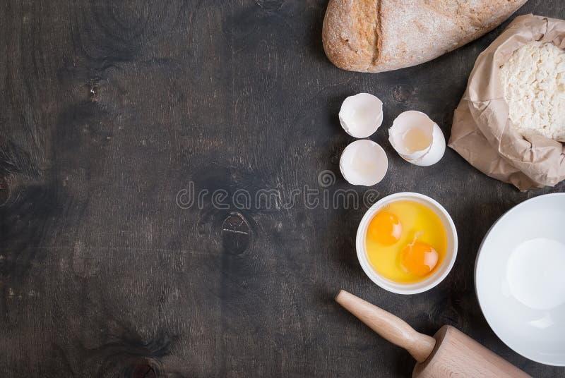 Stekhet bakgrund med äggskalet, bröd, mjöl, kavel