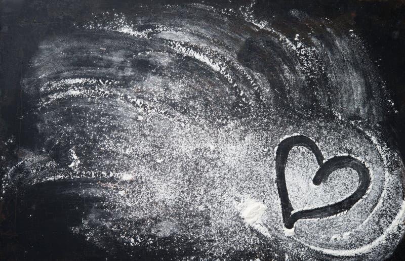 Stekhet bakgrund med hjärtaform och mjöl på den mörka tabellen arkivfoton
