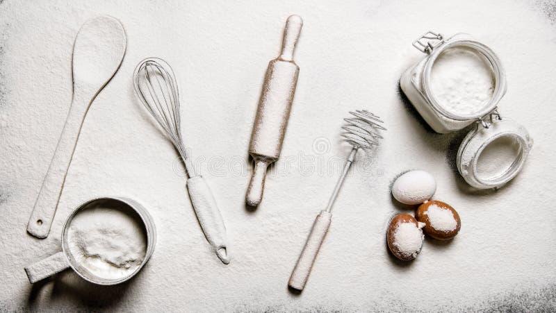Stekhet bakgrund Mjöl, ägg och olika hjälpmedel - drevkarlar, spatel, kavel och en sikt royaltyfria bilder