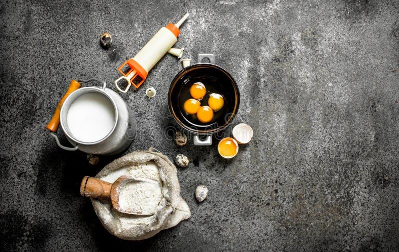 Stekhet bakgrund Mjölka, pudra, ägg och konfektinjektionssprutan för kaka royaltyfria bilder
