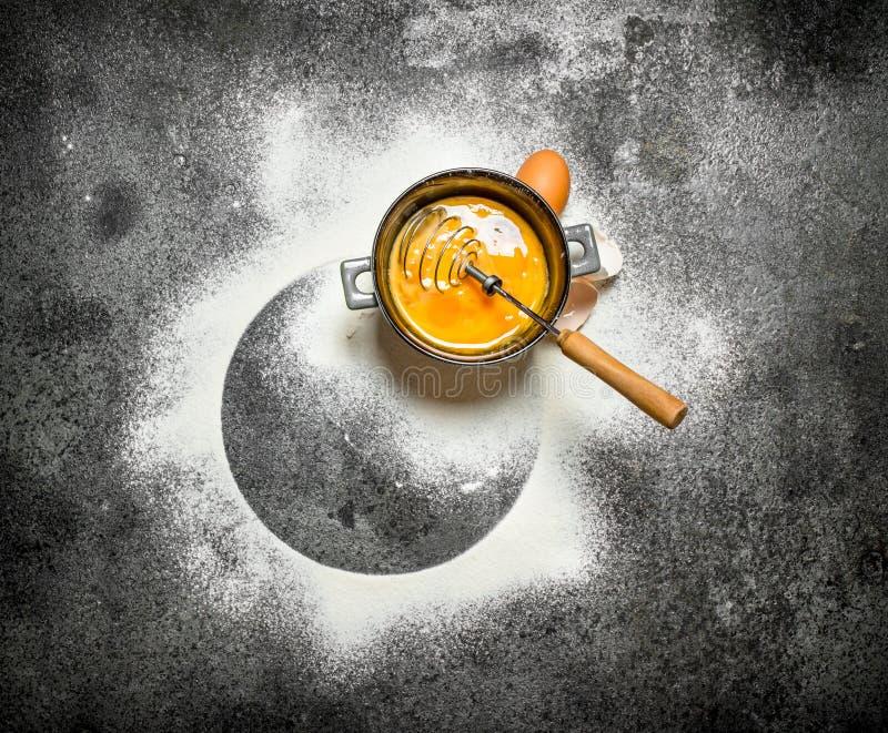 Stekhet bakgrund Vifta äggen med det siktade mjölet arkivbilder