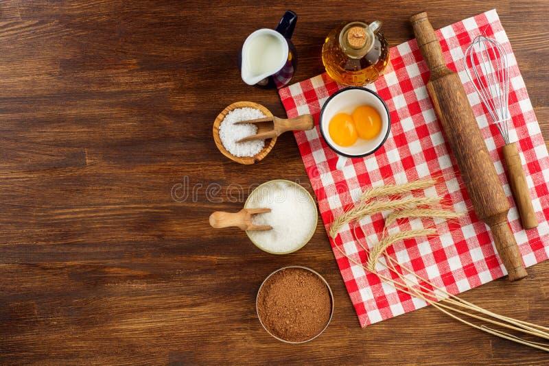 Stekhet kaka i lantligt kök - ägg för degreceptingredienser, mjöl, mjölkar, breder smör på, sockrar på vit planked trä arkivbild