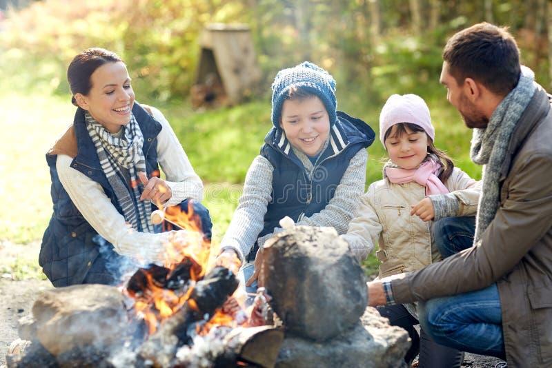 Stekhet marshmallow för lycklig familj över lägereld arkivbilder