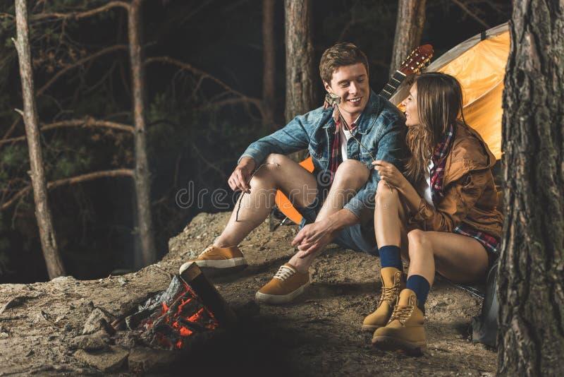 stekhet marshmallow för lyckliga par på pinnar royaltyfria bilder
