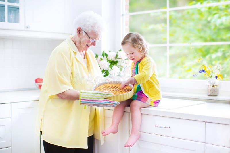 Stekhet paj för farmor och för gullig flicka i vitt kök royaltyfri fotografi