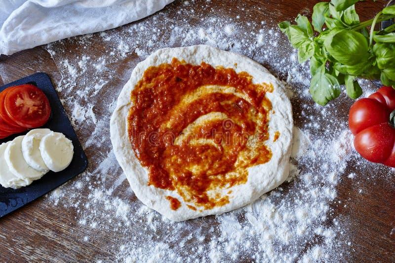 Stekhet pizza rullande ut deg med sås royaltyfri bild