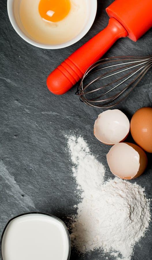 stekheta ingredienser (ägg, mjöl, mjölkar, äggskalet och kavlen), fotografering för bildbyråer