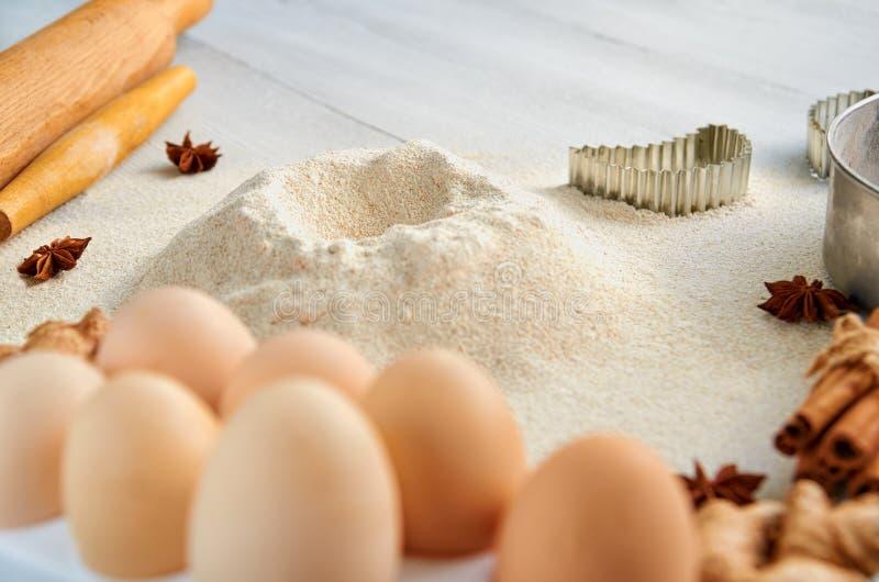 Stekheta ingredienser för deg på den gråa tabellen: kavel, ägg, ingefära, anisstjärnor, kanel och bakewares Stekhet bakgrund royaltyfria foton