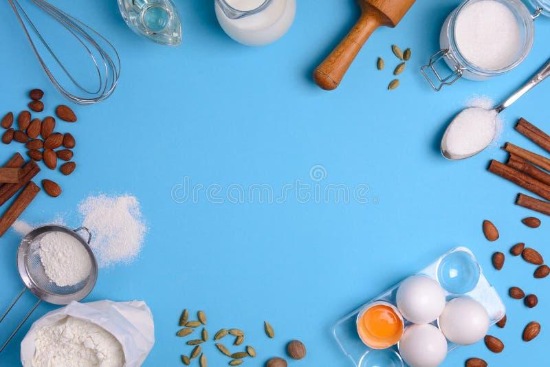 Stekheta ingredienser för hemlagad bakelse på blå bakgrund Baka det söta kakaefterrättbegreppet Top beskådar Lekmanna- lägenhet arkivfoto
