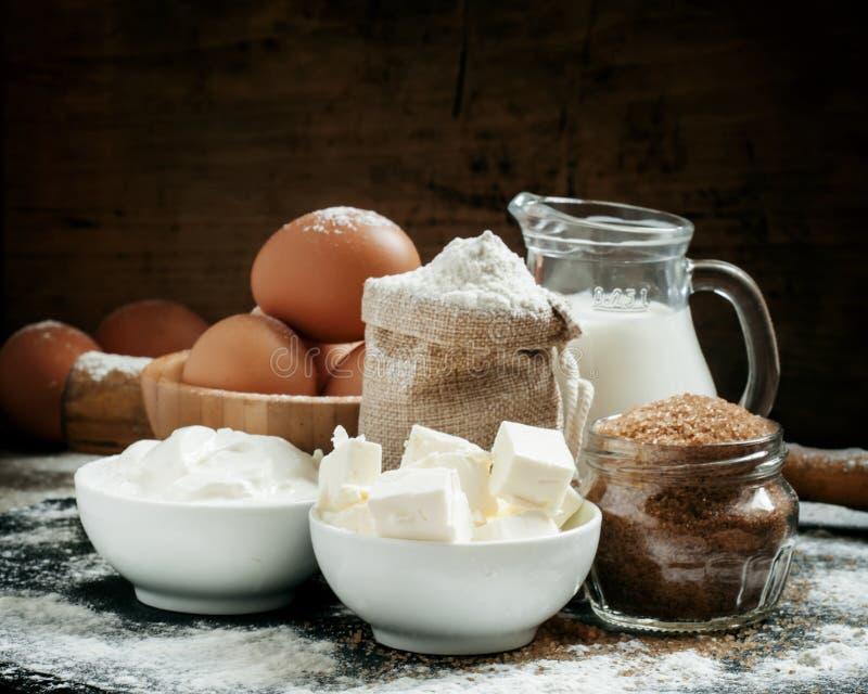Stekheta ingredienser: mjölka, breda smör på, pudra, sockra, ägg och rullningen royaltyfria bilder