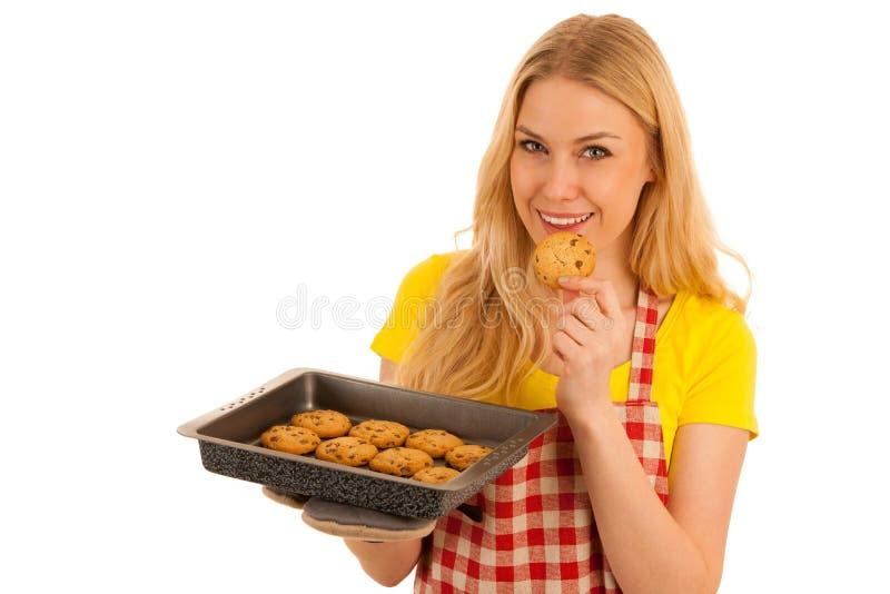 Stekheta kakor för ung kvinna som isoleras över vit bakgrund royaltyfri bild