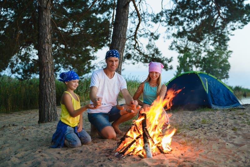 Stekheta korvar för lycklig familj över lägereld campa och turismbegrepp royaltyfria bilder