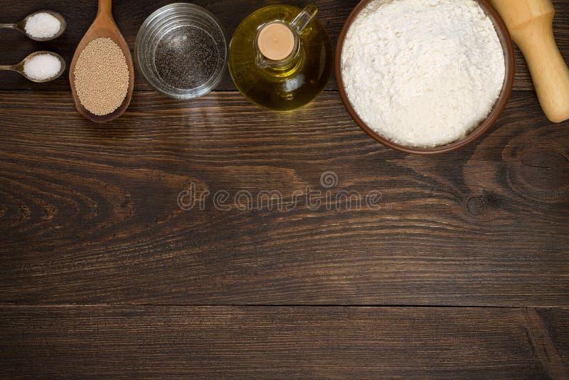 Stekheta redskap och ingredienser för pizzadeg på träbakgrund arkivfoton
