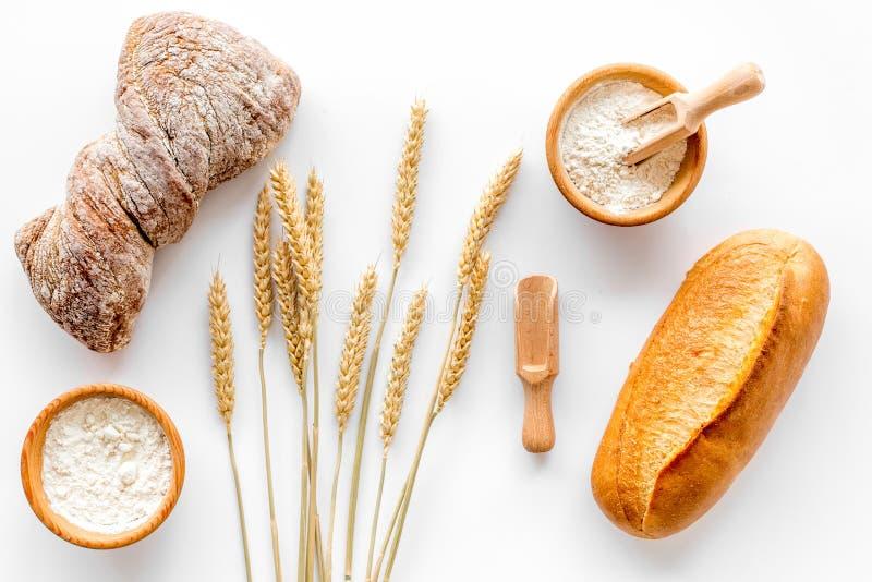Stekhett bröd med vetemjöl och öron på sikt för vit bakgrund för tabell bästa royaltyfri bild