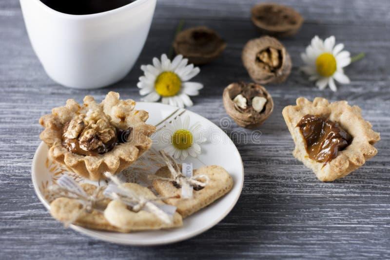 stekhett hemlagat Kondenserade Shortcakedegkorgar med valnötter och mjölkar royaltyfri foto