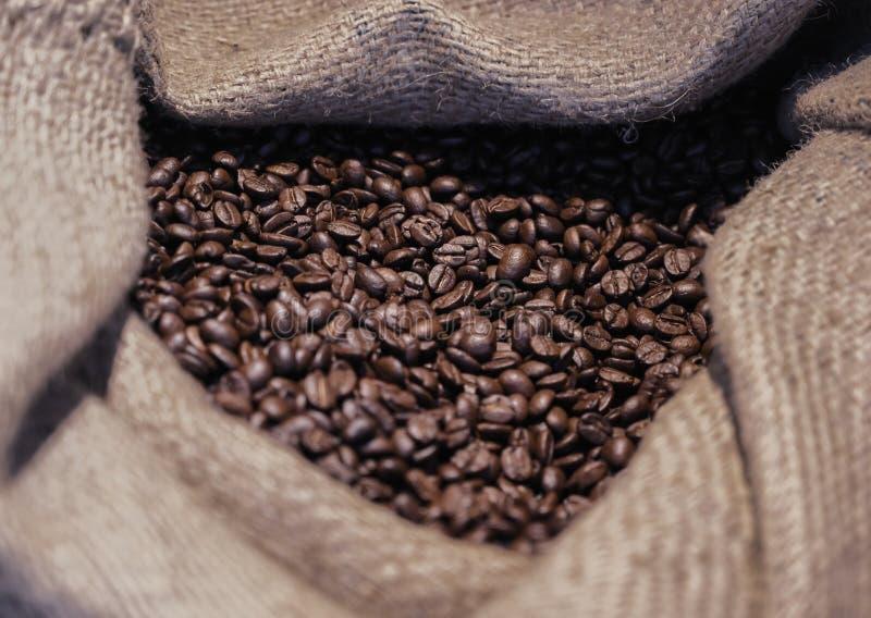 Stekkaffeböna i säck arkivfoton