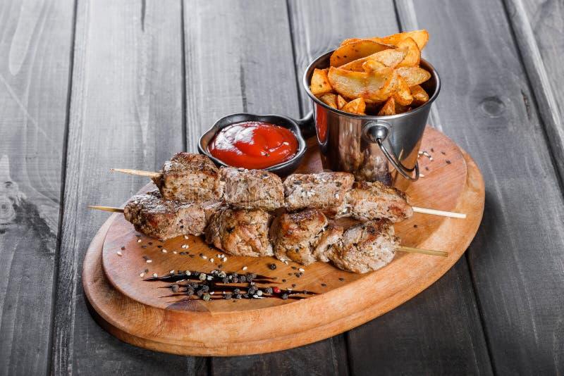 Steknålar av kött med sås- och potatissmåfiskar i en hink på träskärbräda arkivbild