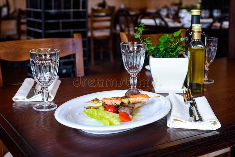 Steknålar av laxen och tonfisk med körsbärsröda tomater och sallad spricker ut arkivbild