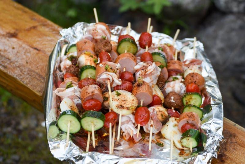 Steknålar med grönsaker och korv, bacon och köttbullar arkivfoto