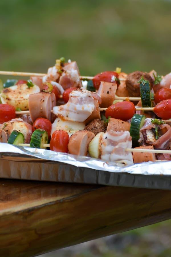 Steknålar med grönsaker och korv, bacon och köttbullar royaltyfri bild