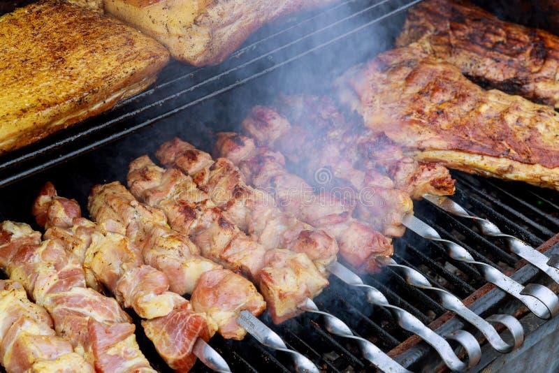 Steknålar med kött på grillfestgallret arkivbilder