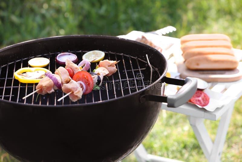 Steknålar med rått kött och grönsaker på grillfestgaller utomhus royaltyfri fotografi