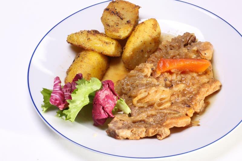 Steknötkött med löken och potatisar  royaltyfri bild