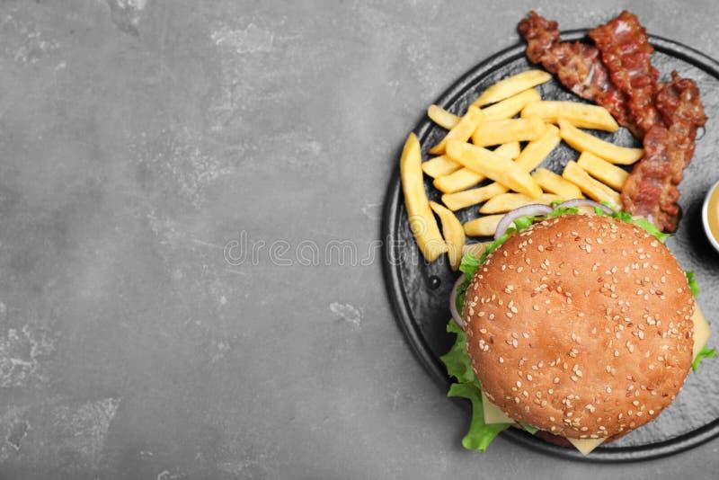 Stekpanna med den smakliga hamburgaren och franska småfiskar på grå bakgrund arkivfoto