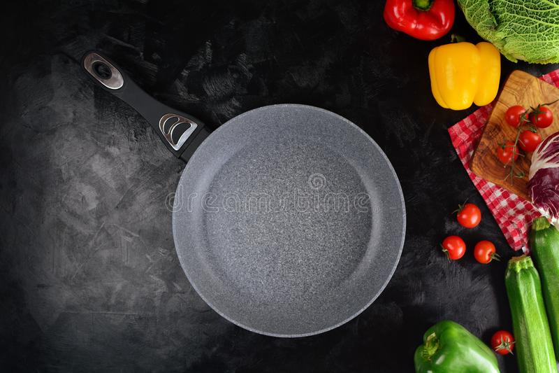 Stekpanna på en svart bakgrund med olika grönsaker royaltyfria foton