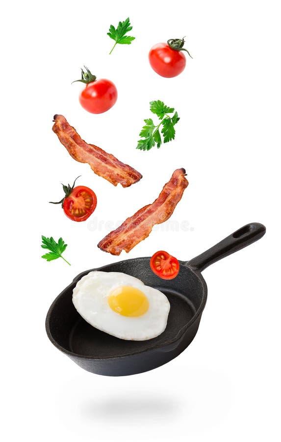 Stekt ägg, bacon och körsbärsröda tomater som flyger in i järnkastrullen royaltyfria foton