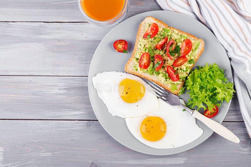 Stekt ägg för frukost, grönsaksallad och en grillad avokadosmörgås på en grå bakgrund arkivfoto