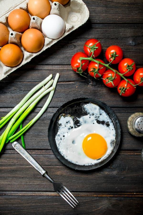 Stekt ägg i en panna med en kassett av nya ägg arkivfoto