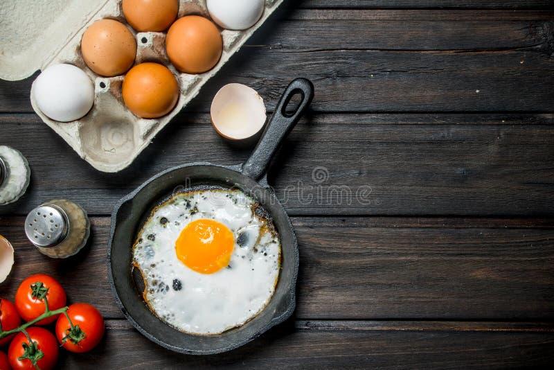 Stekt ägg i en panna med en kassett av nya ägg arkivbild