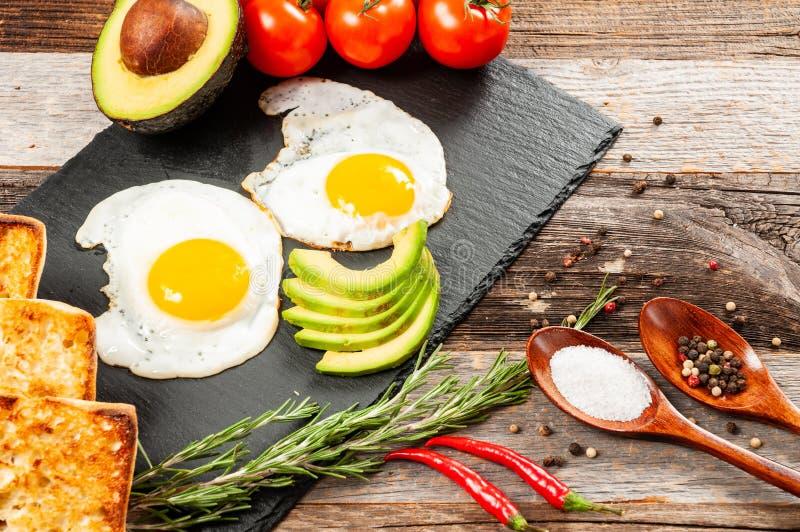 stekt ägg I kursen av framställning av frukosten med stekte ägg och grönsaken royaltyfri bild