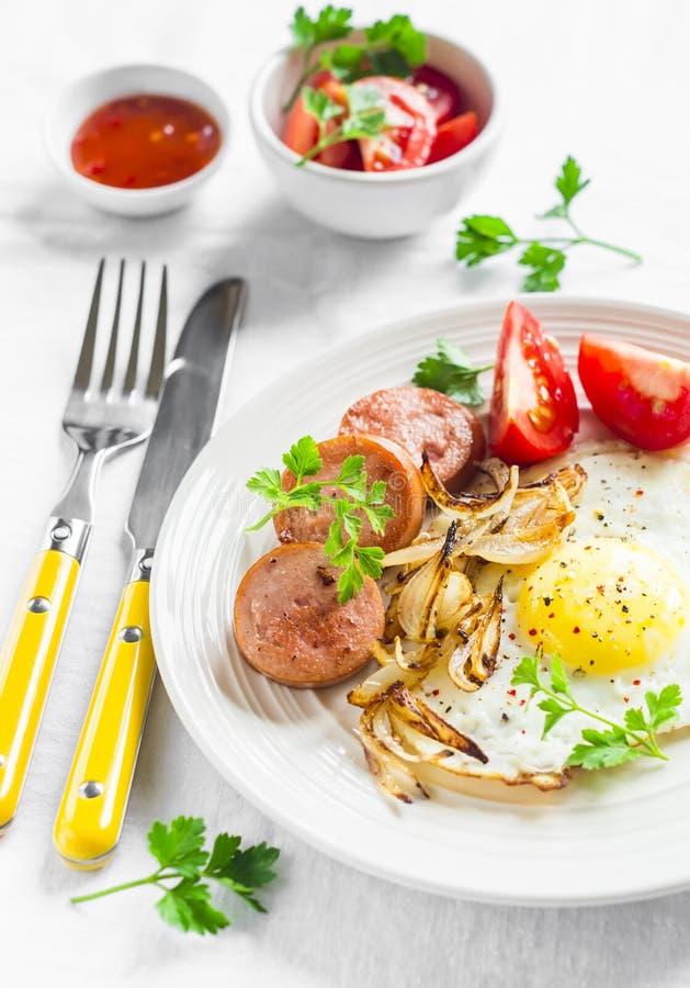 Stekt ägg, korv, tomater - smaklig frukost eller mellanmål, på den ljusa plattan royaltyfri foto