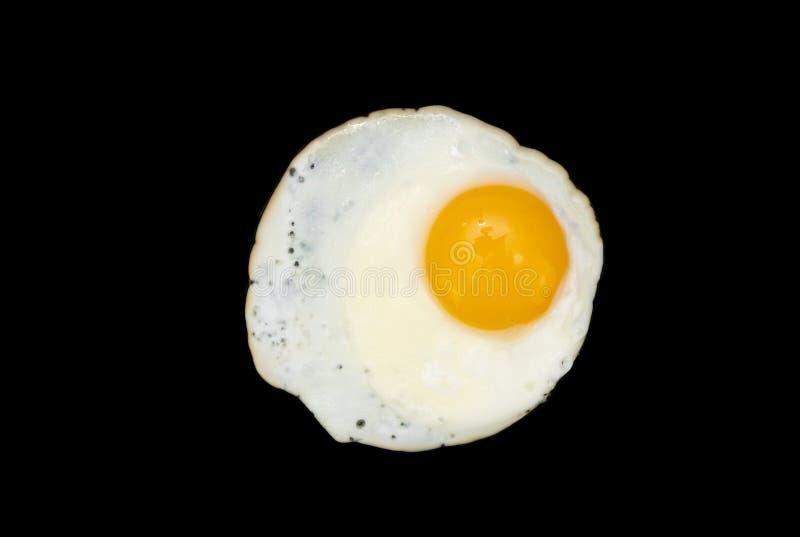 Stekt ägg på en svart arkivbilder