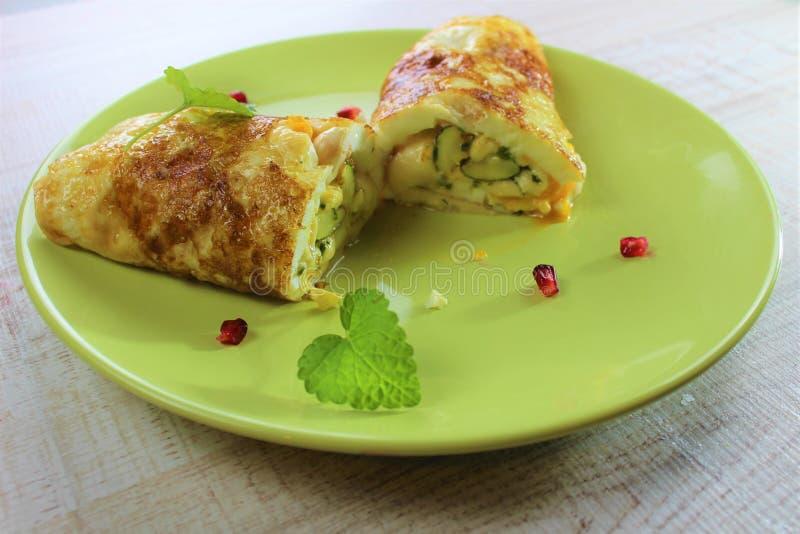 Stekt äggomelett för morgon som frukost är välfylld med zucchinin på den gröna plattan Klippa det med en kniv och en gaffel royaltyfria bilder