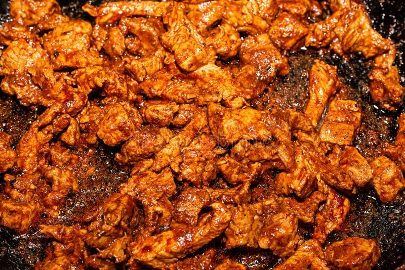 Stekt aromatisk läcker källa för gulasch av protein i en kulinarisk stekpannabakgrund arkivfoton