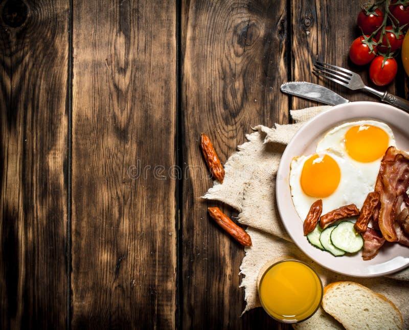 Stekt bacon med ägg och orange fruktsaft royaltyfria bilder