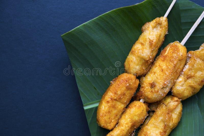 Stekt banan på bananbladplattan Filippinsk efterrättbananstickreplik Guld- banan på pinnen som tjänas som för mat arkivbild