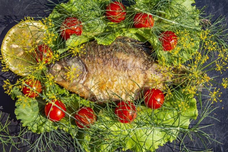 Stekt crucian fisk på en svart bakgrund med grönsaker och citronen arkivfoto