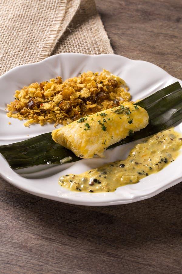 Stekt fisk med farofa- och passionfruktsås - traditionell amazonian maträtt - Filhote caboclo royaltyfria bilder