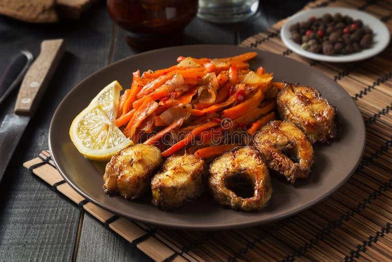 Stekt fisk med grönsaker och citronen royaltyfria foton