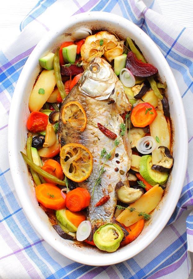 Stekt fisk med grillade grönsaker fotografering för bildbyråer