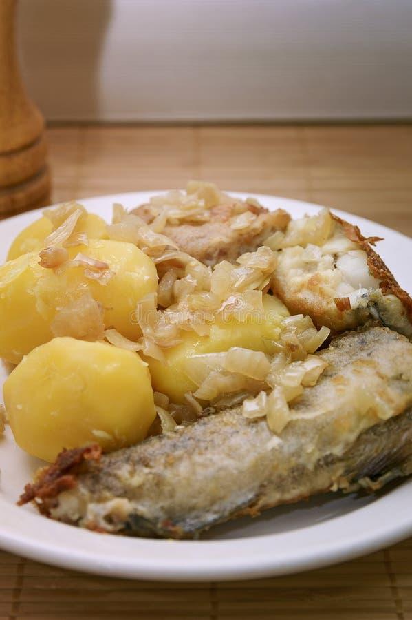 Stekt fisk och kokta potatisar på en platta fotografering för bildbyråer