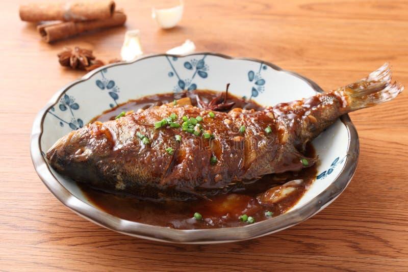 Stekt fisk på den kinesiska plattan på trätabellen i restaurang royaltyfri bild
