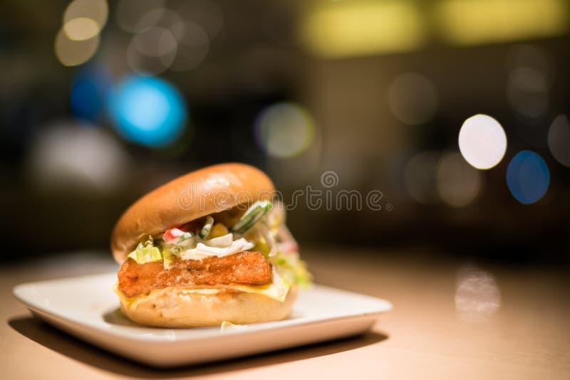 Stekt fiskhamburgare med grönsaken och ost, under strålkastare, bakgrund för suddighetsbokehmörker royaltyfri foto